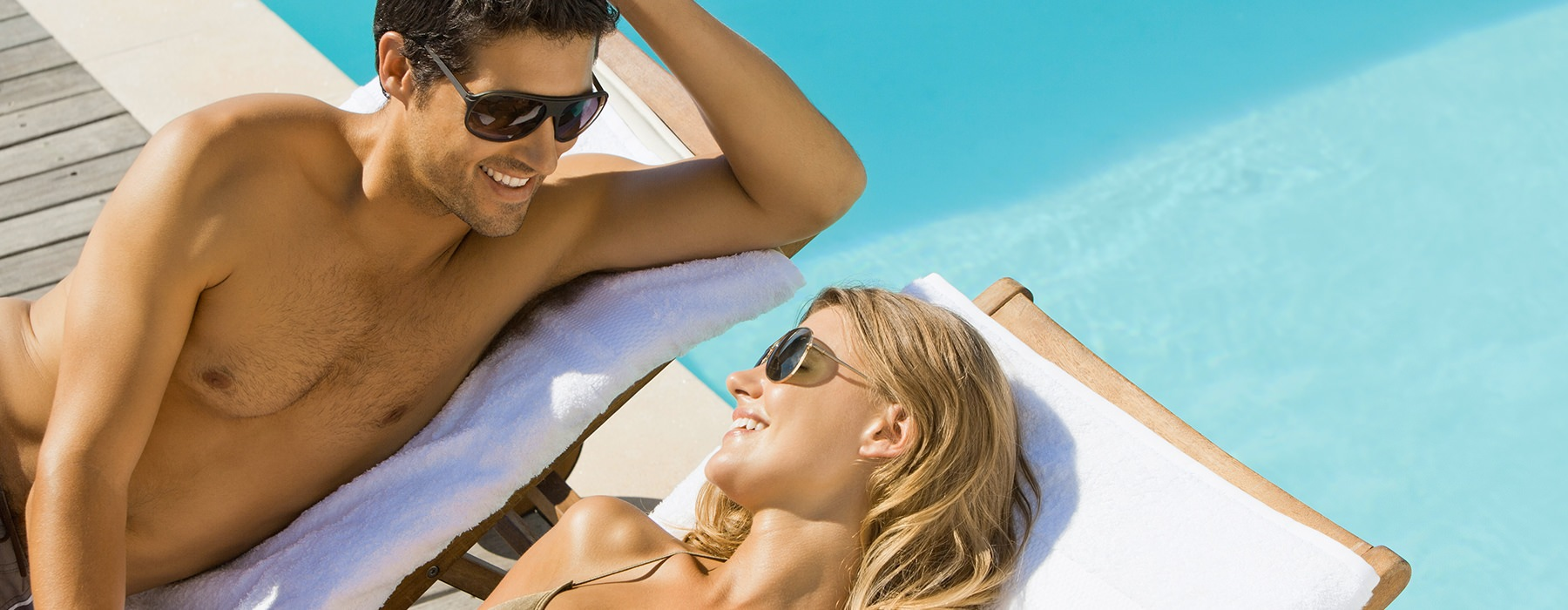 A couple is relaxing next to the pool