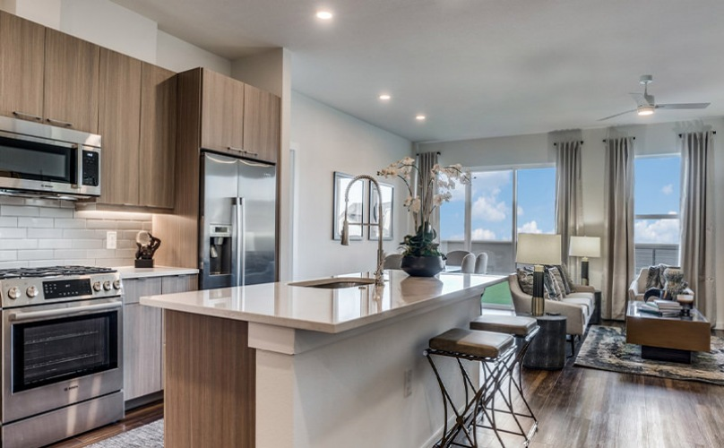 Large well lit kitchen with dark wood floors and granite countertops with stainless steel appliances.