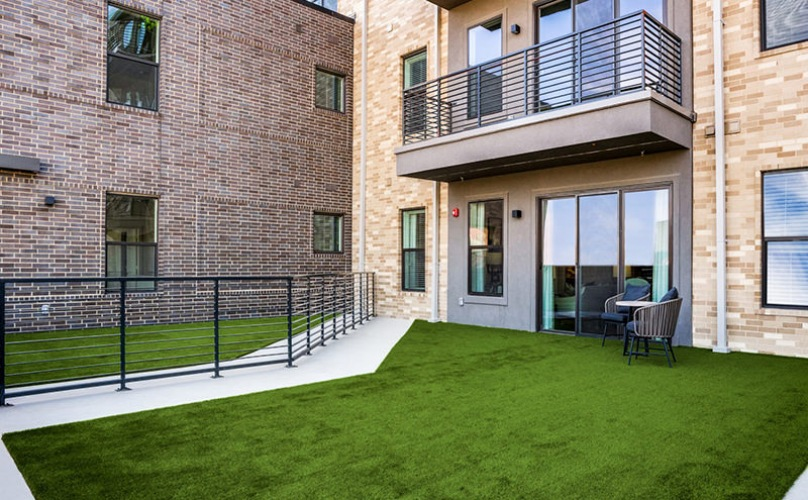 The terrace of The Drake apartments with lush green grass and plenty of room for kids and pets.